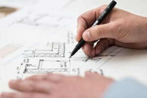 A pair of hands working on a design of a house